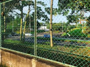 金網のフェンス越しに道路が見える